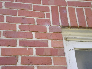 Example of early signs of stress corrosion in lintel causing brick fissures and future spall.